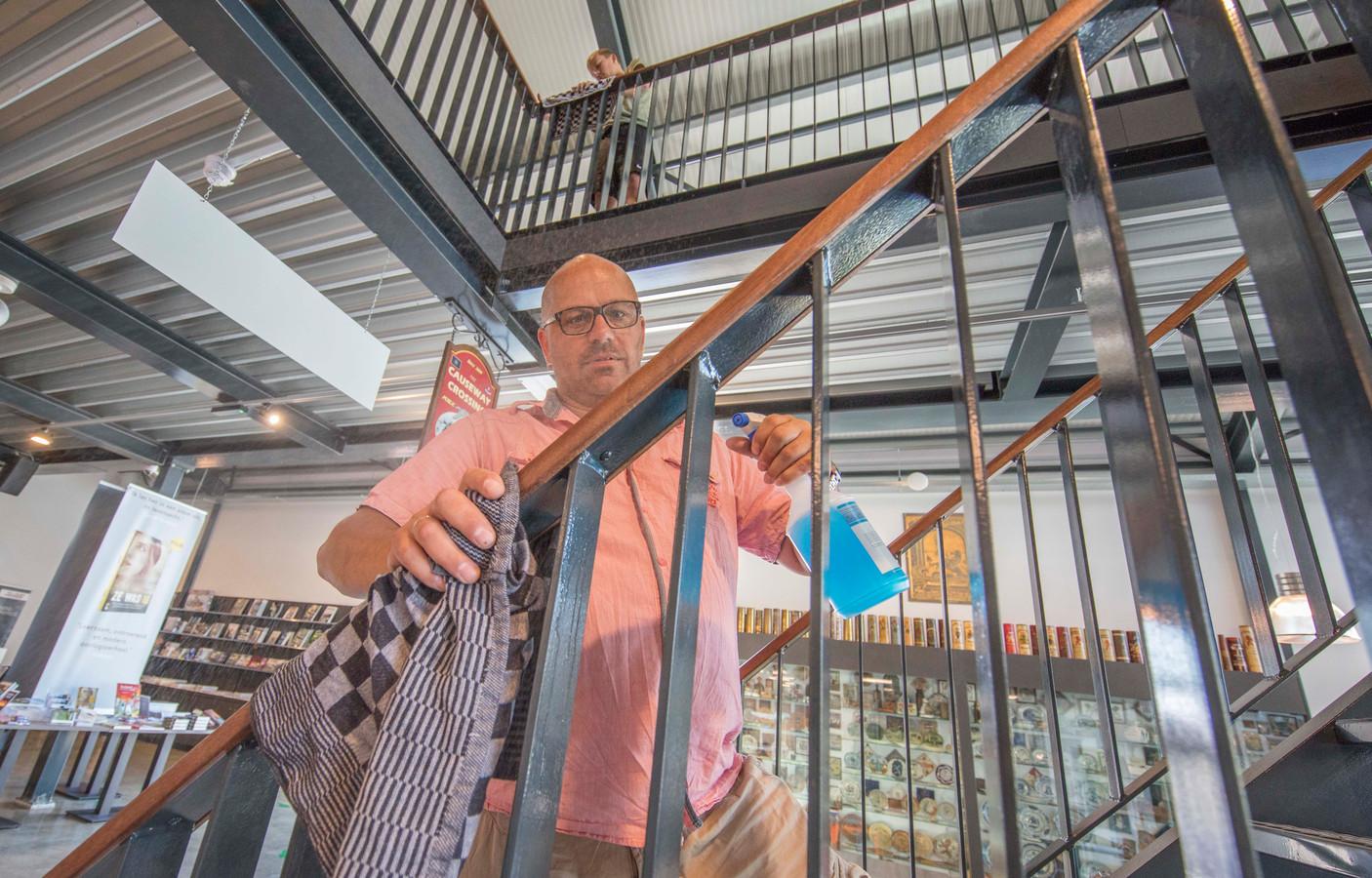 Vrijwilliger Hubert Moerman ontsmet de leuning van een trap. Zijn zoon Mika (ook vrijwilliger) is boven bezig.