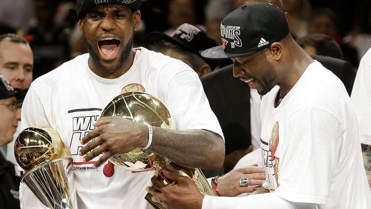Uit 2013: Dwayne Wade (r) monstert de NBA Trophy, die LeBron James samen met de trofee van MVP van de NBA Finals vasthoudt. Hoogdagen voor de Miami Heat.