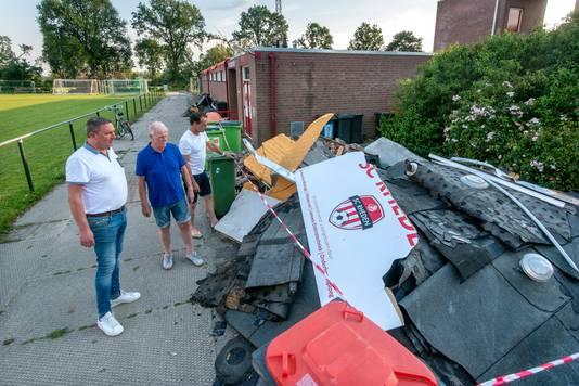 Voorzitter Rick Palm en clubgenoten Wim Janssen en Toon Aalders bij de restanten van het clubgebouw, dat op de achtergrond te zien is (op het dak ligt een oranje zeil). Bovenop de restanten het afgewaaide deel van het scorebord van het hoofdveld.