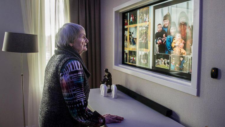 Een dementerende patiënt voor een collage met foto's van haar dierbaren. Beeld Hollandse Hoogte / Koen Verheijden