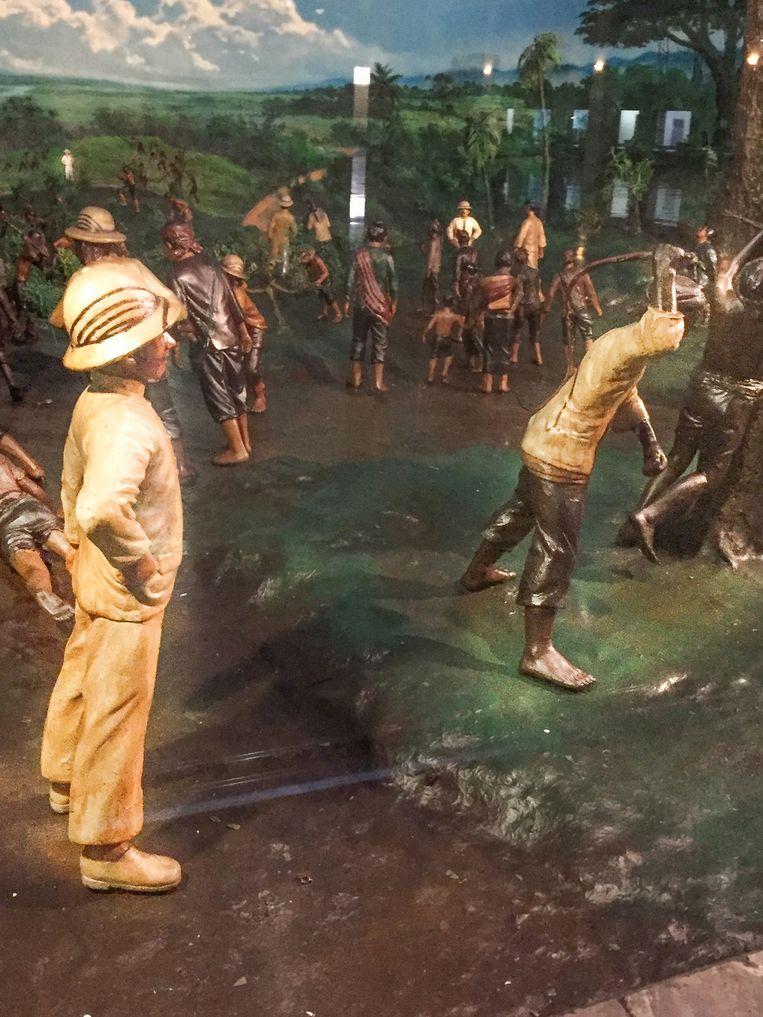 De koloniaal kijkt toe hoe een Indonesiër wordt gegeseld. Beeld