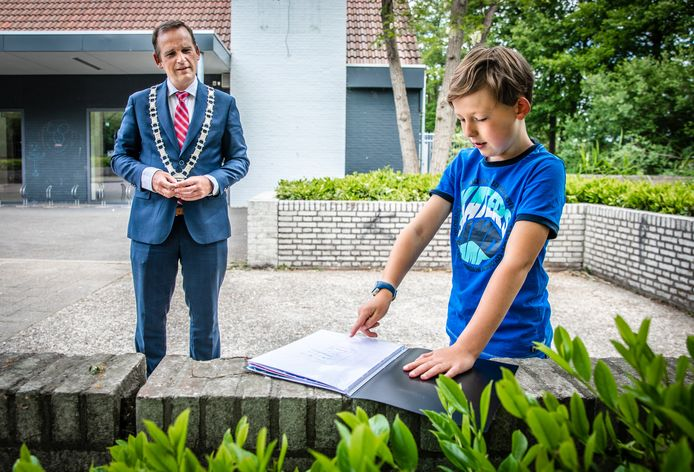 Burgemeester Bram van Hemmen luistert naar het plan van Willem (8) voor een nieuwe speeltuin in Oud-Beijerland.