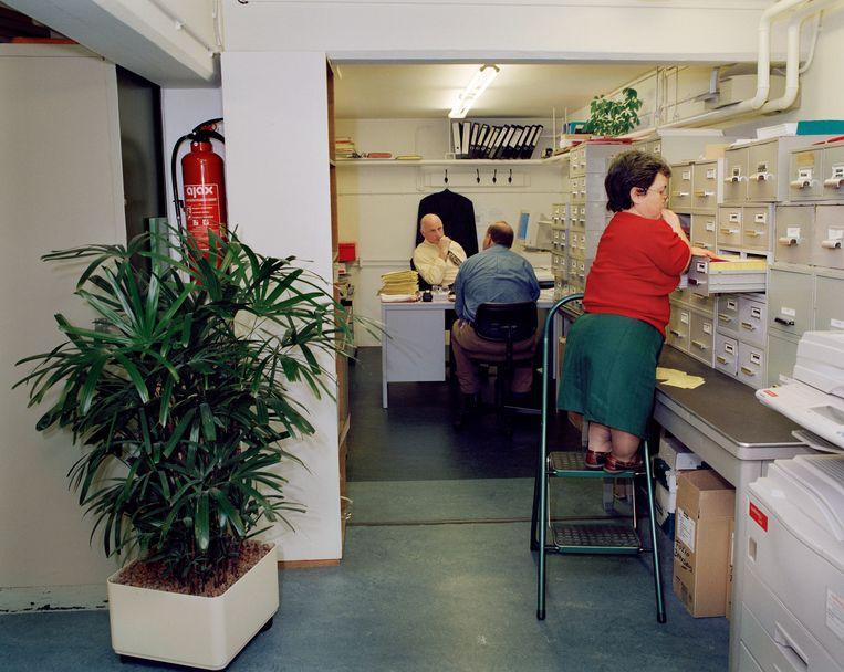 Een werknemer van een Octrooibureau zoekt in de kaartenbak. Uit de serie 'Kantoorcultuur' over klassieke kantoren zonder moderne innovaties, 2007.  Beeld null