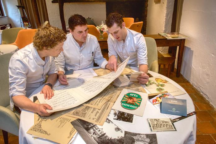 Chef-kok Tonny Berentsen (midden) bekijkt samen met zijn twee souschefs historische knipsels, foto's en menukaarten.