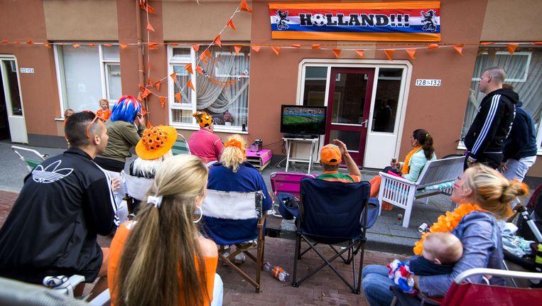 Oranjefans kijken buiten op een televisie naar het WK-duel tussen Australie en Nederland. Beeld anp