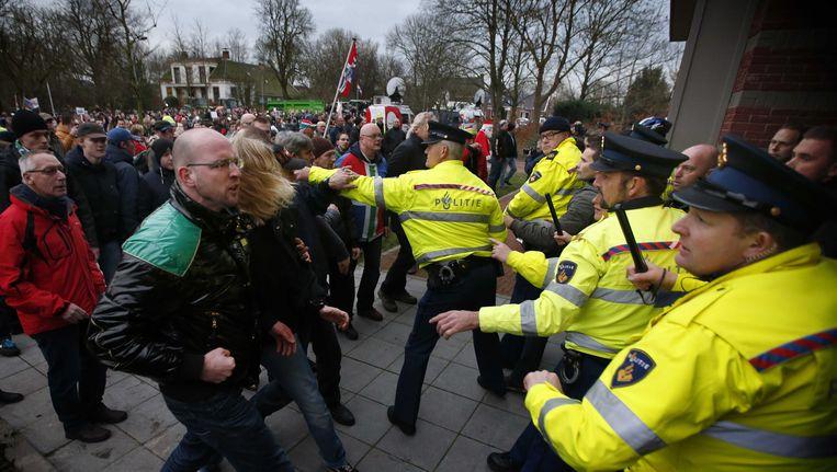 Agenten en boze actievoerders gisteren tijdens de persconferentie van minister Kamp in Loppersum. Beeld ANP
