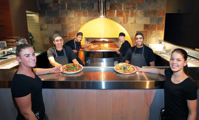 Van links naar rechts Angel, Ronny, Vishal, Percy, Ahmed en Gaby zijn druk bezig met de culinaire pizza's die ze serveren.