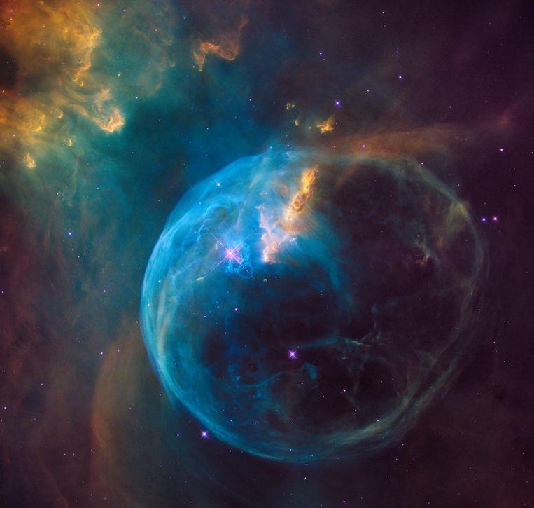 In het midden van deze kosmische bol – ook wel bekend als de zeepbelnevel – huist een grote, jonge ster. Uit de buitenste lagen van die ster waait gas, dat de bol vormt die je op de foto kunt zien. Omdat de ster dat gas verwarmt, begint de bol zelf ook te stralen. Beeld Nasa & Esa