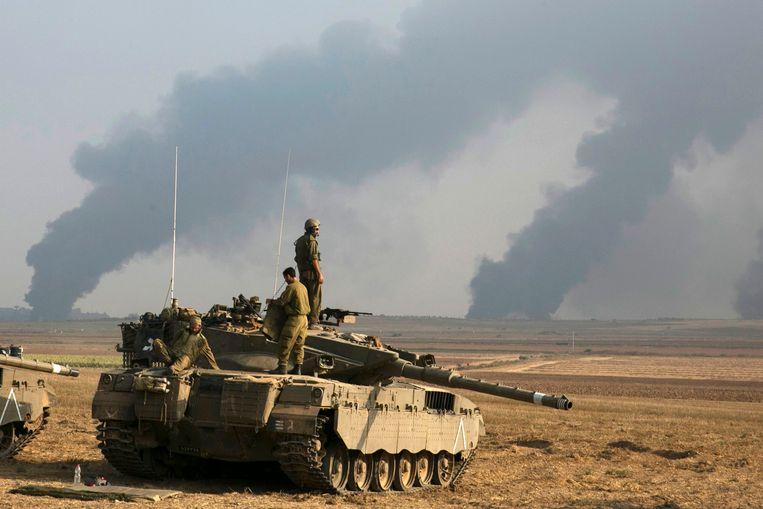"""Israelische soldaten staan boven op een tank vlakbij de noordelijke Gazastrook. De Israëlische luchtmacht heeft deze nacht meerdere doelwitten in de Gazastrook gebombardeerd. Volgens het Israëlische leger werden """"terroristische doelen van Hamas"""" - de islamistische beweging die de plak zwaait in de Gazastrook - in het noorden van Gaza geviseerd. Archieffoto."""