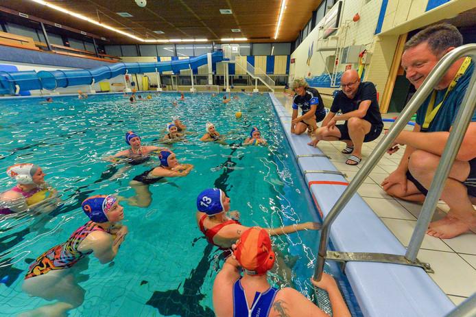 Flinke begeleiding voor de vrouwen van Aquapoldro. Coach Harold Wijngaards (midden) luistert als trainer Ron ter Smitten het woord voert.