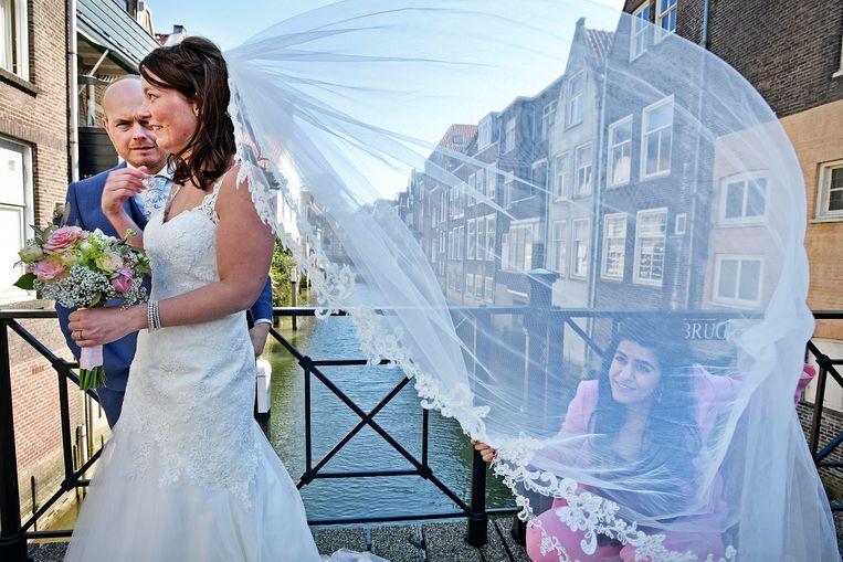 Een stelletje dat gaat trouwen laat de bruidsfoto?s maken op een van de vele bruggen in het oude deel van Dordrecht. Beeld null