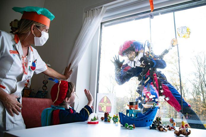 Een Pietje abseilend van het dak van het Amalia Kinderziekenhuis, onderdeel van Radboudumc, blijft hangen bij het raam van de zieke 5-jarige Jonathan uit Geffen.