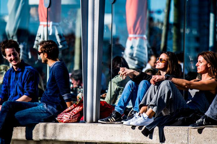 Mensen genieten bij Hotel New York in Rotterdam van de lentezon.