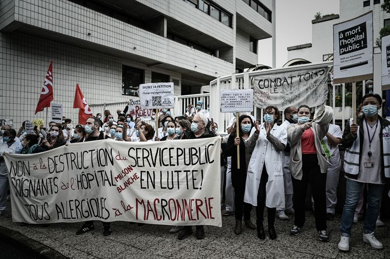Zorgpersoneel met een banier:'Nee tegen de destructie van de publieke diensten. Verzorgers van het ziekenhuis protesteren. Allemaal allergisch voor Macronnerie.' Beeld AFP