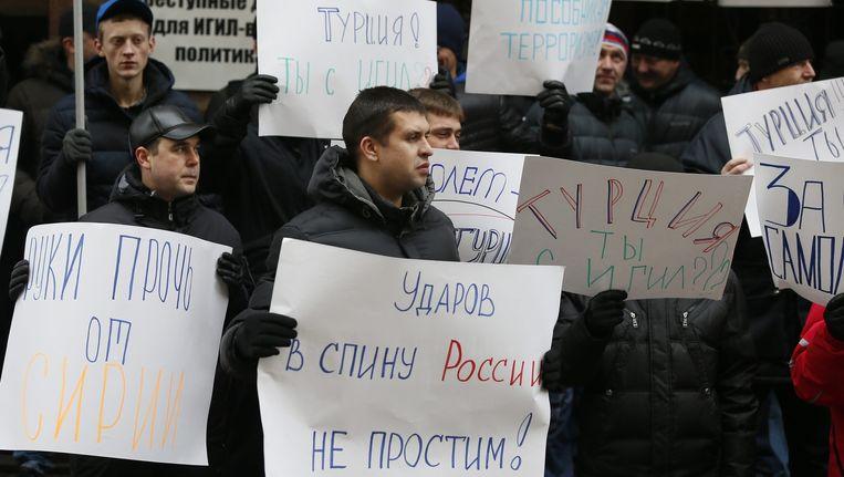 Russen protesteren tegen Turkije. Op de borden valt te lezen: 'Turkije werkt samen met IS', en 'Rusland zal deze dolksteek niet vergeten.' Beeld epa