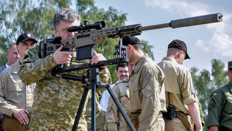 De Oekraïense president Petro Porosjenko inspecteert een wapen tijdens een bezoek op 26 juli aan een militaire schietbaan nabij Kiev. Beeld EPA