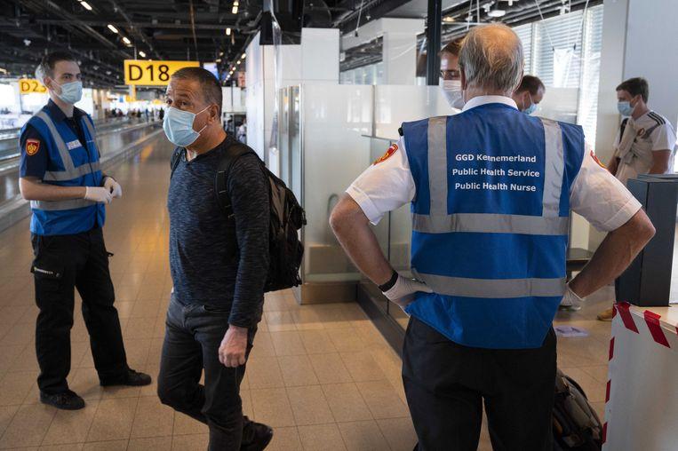 Medewerkers van de GGD ondervragen reizigers op luchthaven Schiphol.  Beeld ANP