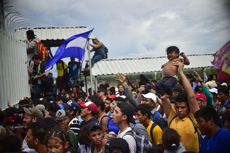 Hondurese migranten beklimmen de poort van grensovergang bij Ciudad Hidalgo. Beeld AFP