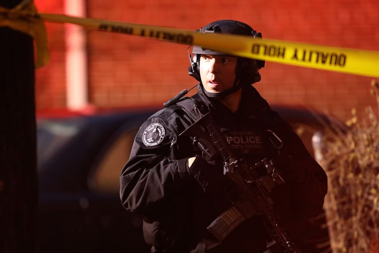 Een zwaarbewapende agent bij een van de afzettingen rond de supermarkt. Beeld Getty Images