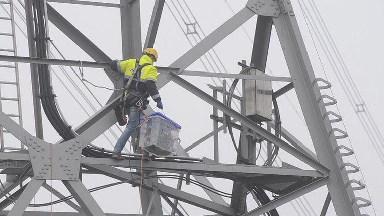 Een Tennetmedewerker ontmantelt een zender die op 80 meter in een elektriciteitsmast is bevestigd. Beeld rtv drenthe
