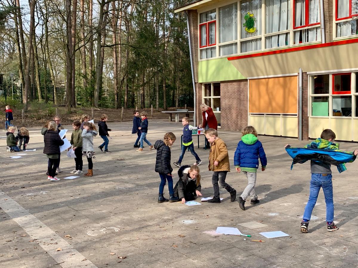 Kinderen uit groep 3 hebben rekenles op het schoolplein.