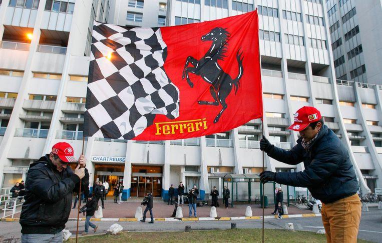 Fans staan met een Ferrari-spandoek voor Schumacher bij het ziekenhuis in Grenoble. Beeld reuters