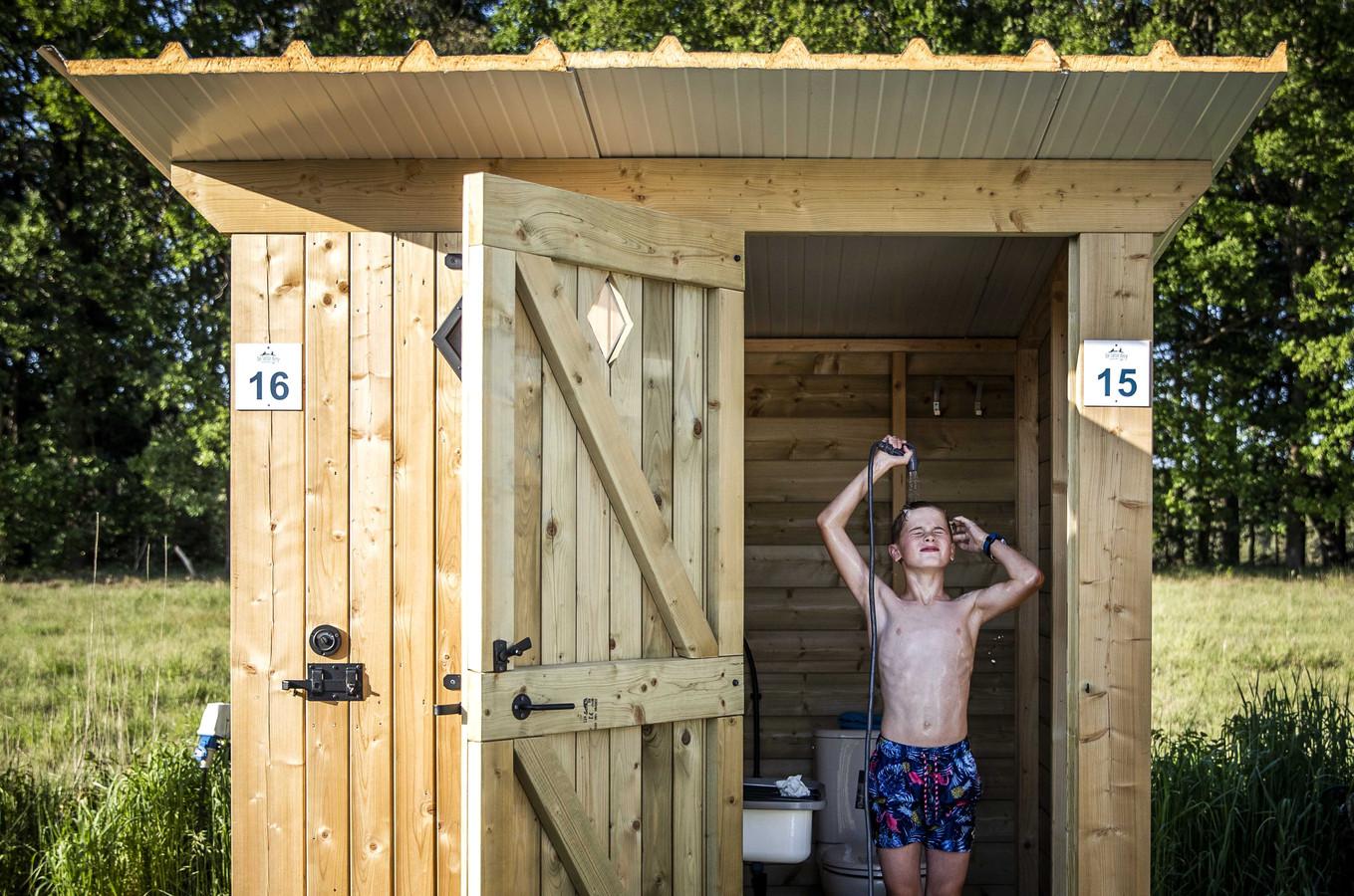 Campinggast Floris maakt gebruik van het prive-sanitair bij de kampeerplek op camping de Solse Berg. Om te voldoen aan de coronaregels zijn er houten huisjes met toilet en zonnedouche geplaatst.