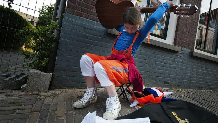Een meisje vertoont haar Jimi Hendrix-kunsten vrijdag op de Utrechtse Vrijmarkt. De Vrijmarkt is traditiegetrouw op de avond voor Koninginnedag van start gegaan en gaat de hele nacht en koninginnedag door. Foto:anp Beeld anp