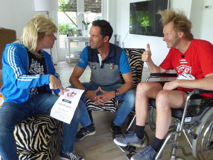 Thijs Kemperink (l.) en zittend lid Laurens ten Den (r.) van de supportersclub Stokkum-Oost dringen Bas Nijhuis op om mee te doen aan de Grote FC Twente Degradatie Show.