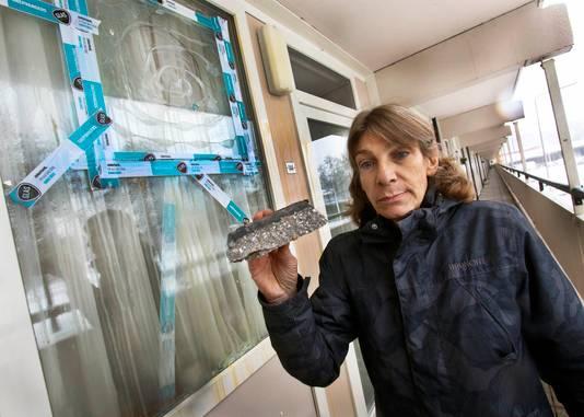 Drie weken geleden: Edith de Waal toont de steen die door de ruit van haar woning ging.   foto : Gerard van Offeren