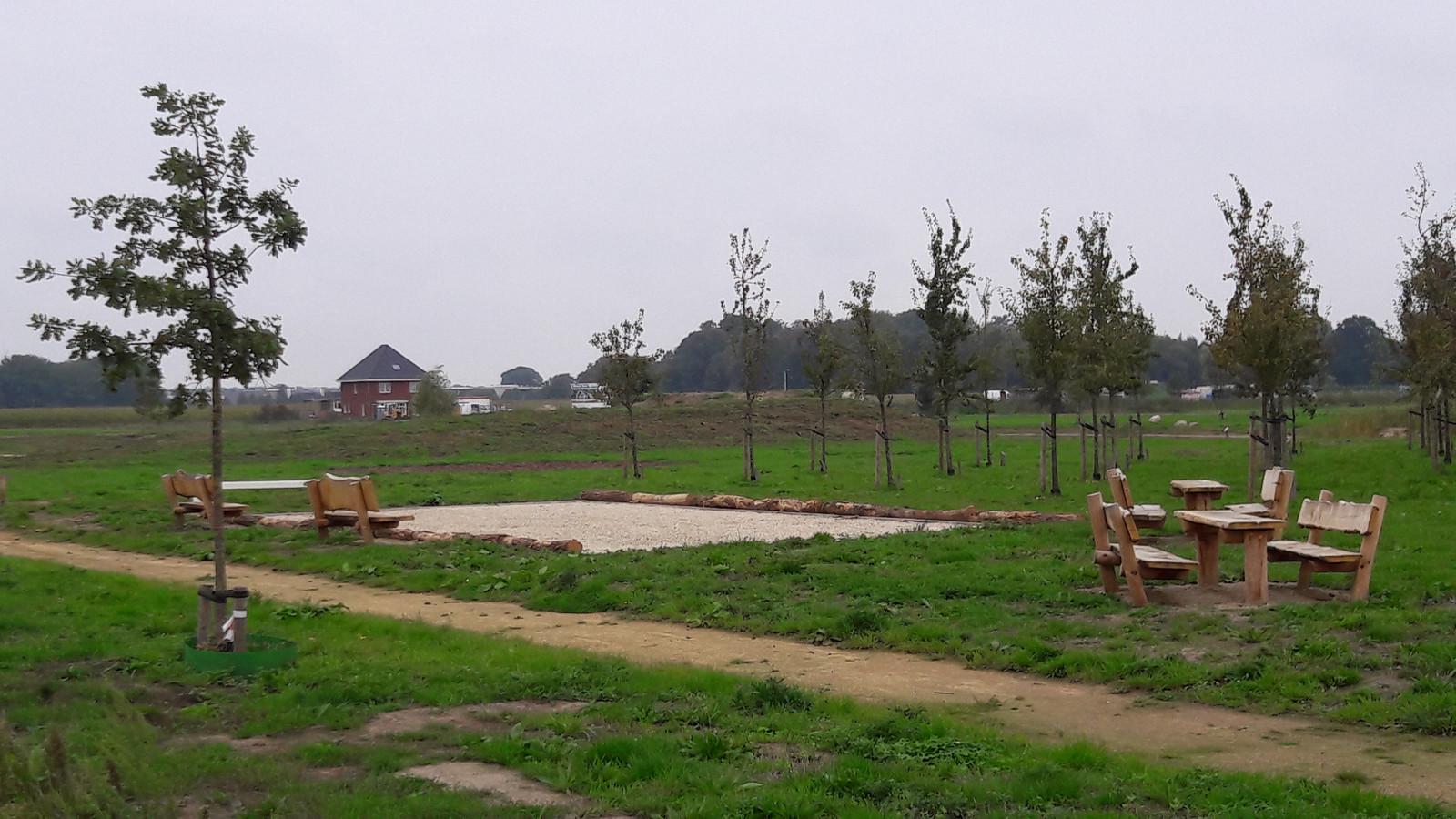 Het omstreden informatiecentrum in het Geerpark in Vlijmen zou moeten komen op de plaats tussen de achterste rij fruitbomen en de buurtheuvel.