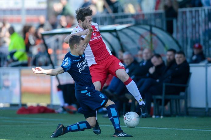 Boyd Lucassen van Jong Vitesse zet Danny van den Meiracker van IJsselmeervogels de voet dwars. De rechtsback van Jong Vitesse was op proef bij Go Ahead Eagles.