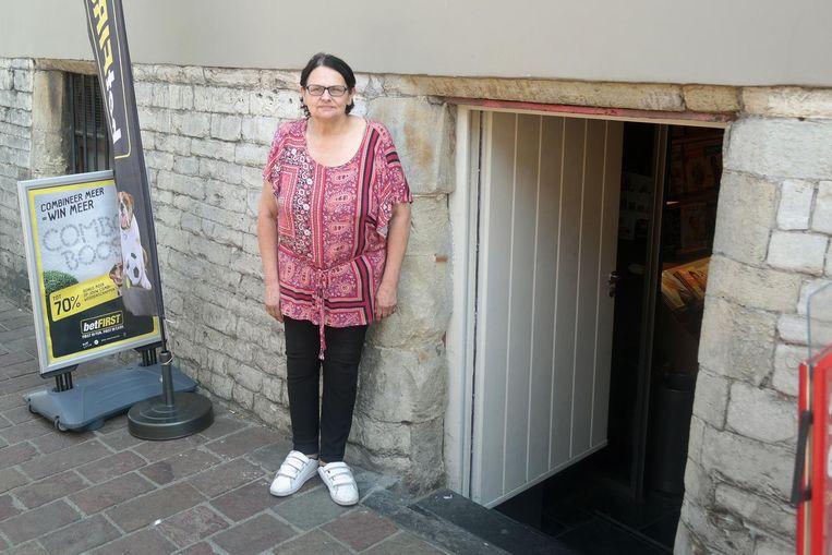 Christiane voor de krantenwinkel van haar zoon.