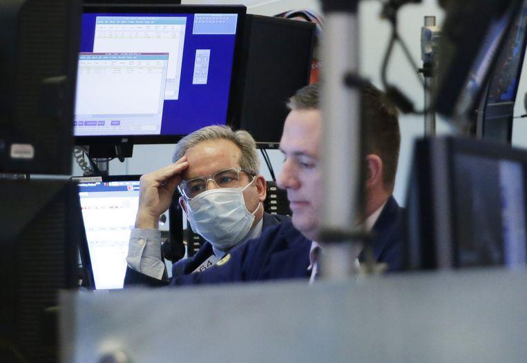 Een handelaar met mondmasker op de vloer van de New York Stock Exchange vrijdag. Inmiddels is de NYSE gesloten en is er enkel elektronische handel mogelijk nadat twee beursmensen besmet bleken met corona.