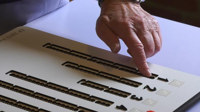 De stemmal heeft getallen in braille en gaatjes voor iedere kandidaat, waar met het rode potlood een keuze kan worden gemaakt.