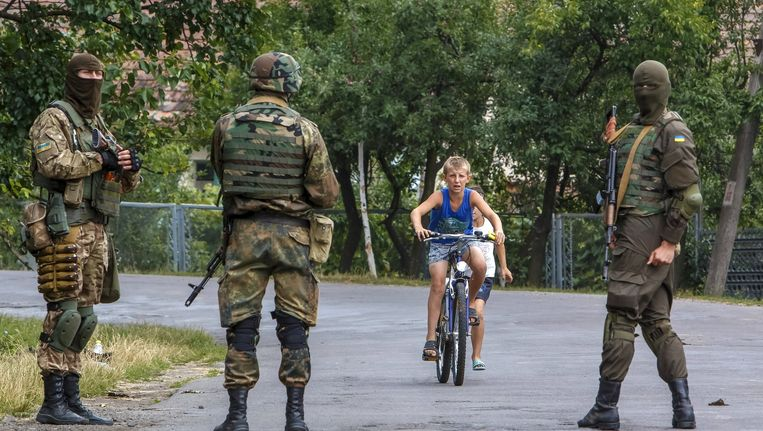 Oekraïense soldaten zoeken naar de daders van een schietpartij bij het stadje Moekatsjeve. Beeld reuters