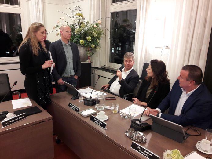 Anne-Cristien Spekle (VVD) en Carlo van Esch (PGB) voeren tijdens een van de vele schorsingen overleg met de wethouders Peter Smit, Stefanie Vatta en Dion Dankers (vlnr)