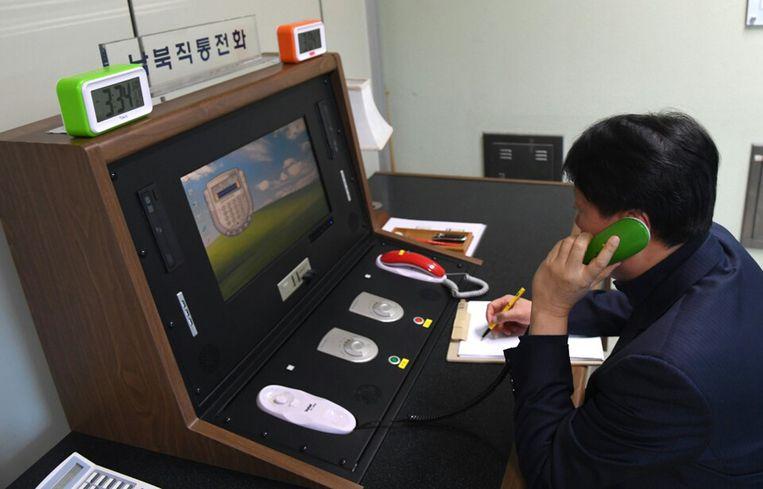 Een Zuid-Koreaanse ambtenaar belt woensdag via de herstelde 'hotline' met een collega in Noord-Korea, om de lijn te testen. Beeld null