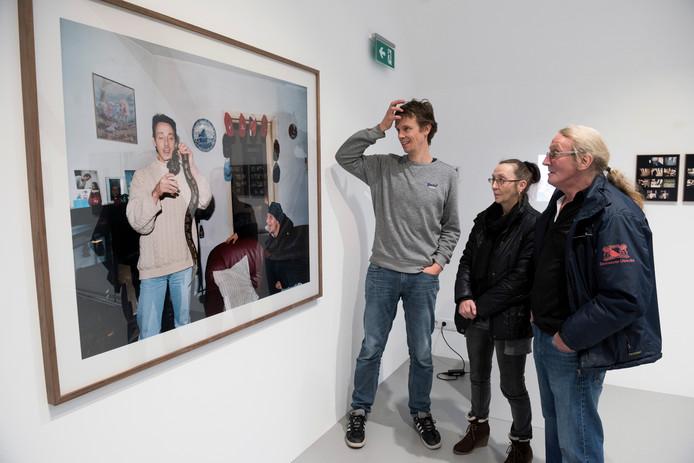 Zus Miep en broer Reinier (r.) kijken naar de foto van Kid met zijn slang. Links staat oud-buurman/fotograaf Rob Hornstra die het roerige leven van de Utrechtse volksjongen vastlegde.