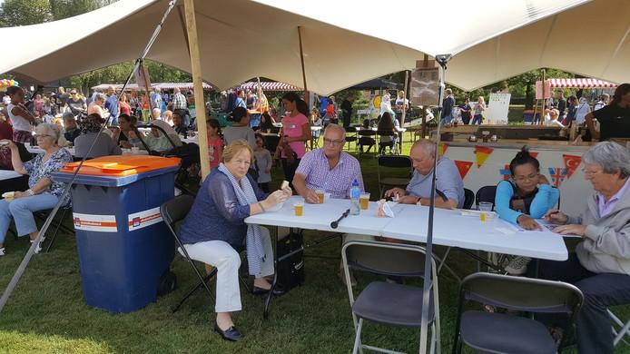 Senioren drinken en kletsen wat op de terrassen van het buurtfeest in de Bossche kruiskamp.