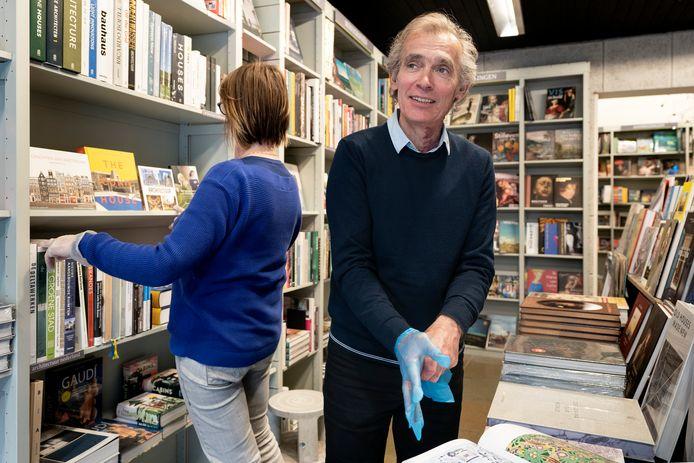 André Stikkers van boekhandel Adr. Heinen in Den Bosch trekt  zijn coronahandschoenen aan om wat boeken  te verplaatsen.