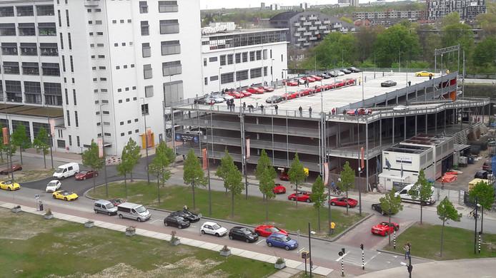 De parkeergarage naast het Klokgebouw (links) op Strijp-S in Eindhoven - hier met bezoek van een groot aantal Ferrari's - gaat dicht en wordt afgebroken. Hier verrijst straks een kantoor- en woongebouw van zeven bouwlagen.