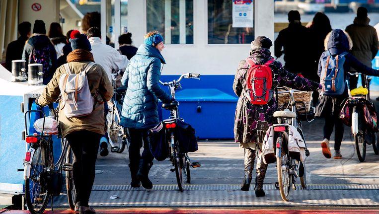 Dik ingepakte fietsers trotseren de kou bij de pont in Amsterdam Noord. Beeld anp