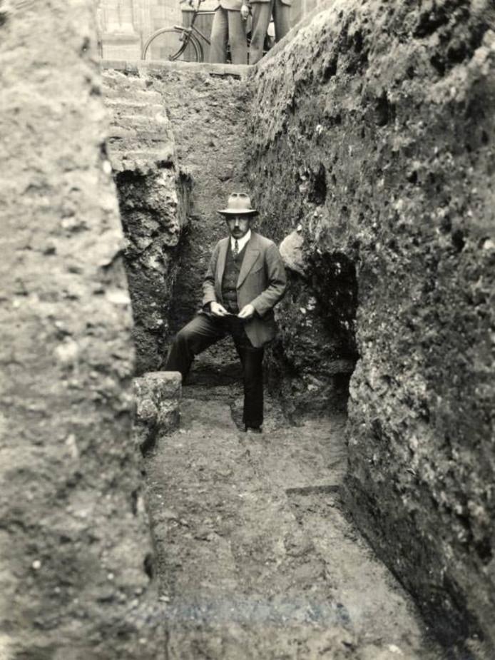 W. Stooker, hoofd gemeentewerken in een werkput tijdens opgravingen op het Domplein.