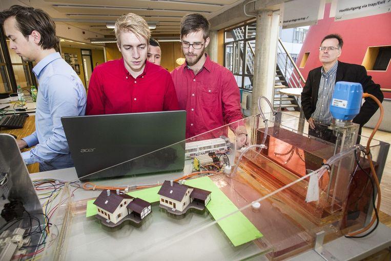 Op een computersimulator kunnen Haagse studenten hacks oefenen en tegenhouden. Aan deze computer is een schaalmodel gekoppeld van een poldertje dat onder water loopt. Beeld Arie Kievit