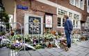 Voorbijgangers bij de bloemenzee voor het advocatenkantoor van de vermoorde Derk Wiersum.