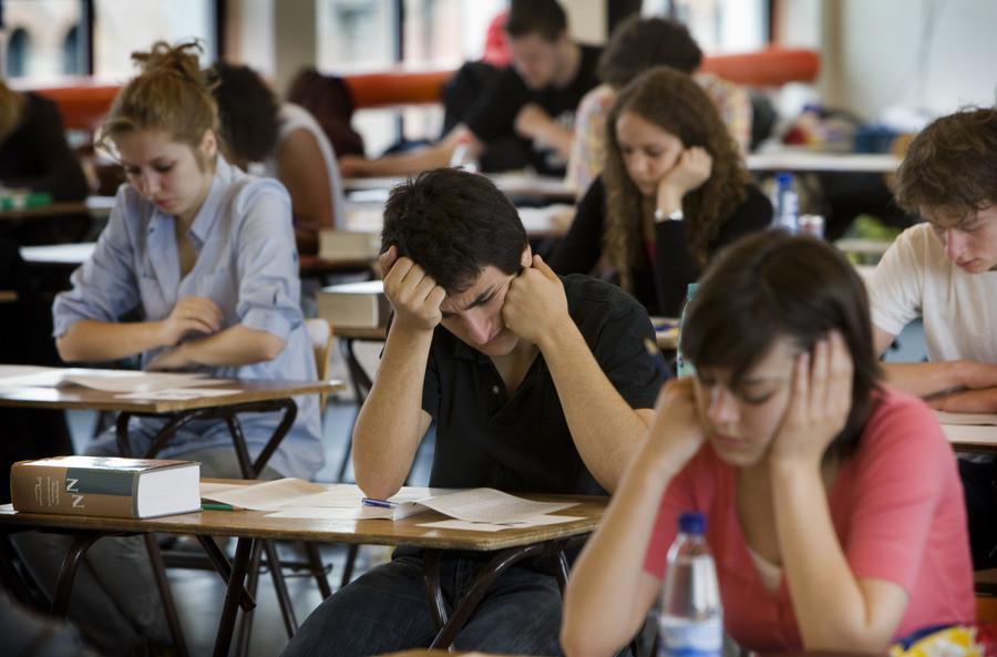 Leerlingen buigen zich over hun eindexamen.
