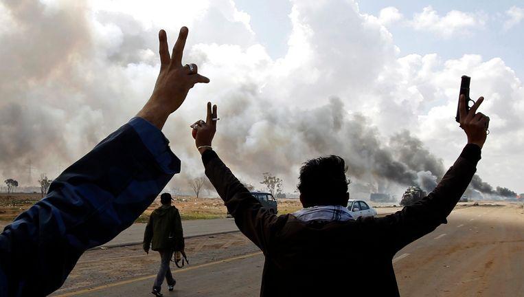 Opstandelingen zwaaien naar een brandend voertuig dat werd geraakt door internationale bombardementen. Beeld reuters