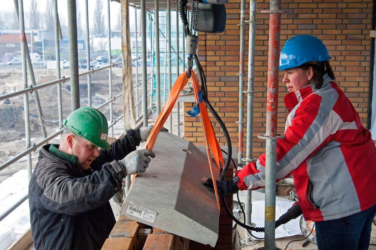 Een man en vrouw plaatsen een prefab afdekband met een kraan op de muur van het toekomstige balkon.  Beeld Nederlandse Freelancers