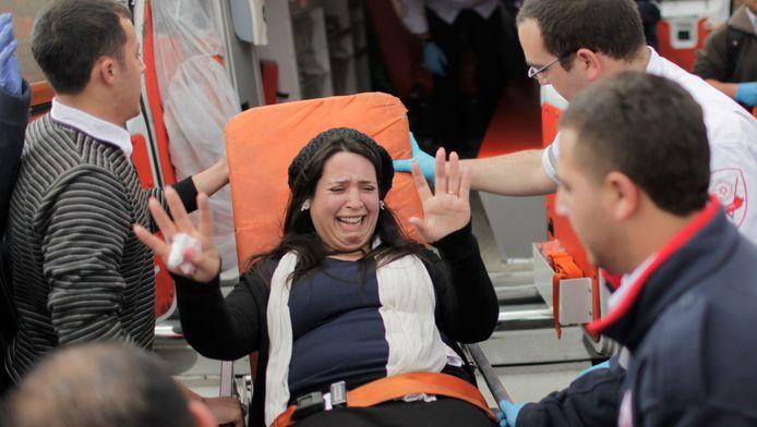Een Israëlische vrouw wordt door reddingswerkers geholpen na een bomexplosie.